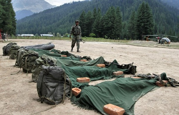 GUREZ, KASHMIR, INDIA - AUGUST 20: Indian Army soldiers stand guard in front the ammunition and bodies of suspected militants killed by the Indian Army on August 20, 2011 in Gurez, Kashmir, India. The Indian Army has claimed to have foiled an infiltration bid by killing at least 12 militants today in North Kashmir's Gurez sector near the Line of Control, which divides Kashmir between India and Pakistan. A senior Indian Army officer was also killed while two troopers were wounded in the firing by militants who tried to infiltrate by water using a dinghy, an Indian ministry spokesman said.  (Photo by Farooq Khan-Pool/Getty Images)